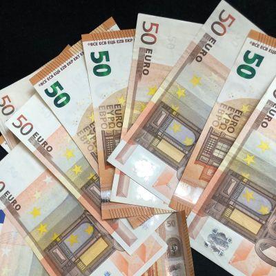 Flera 50 euros sedlar utspridda över svart bakgrund