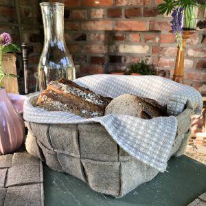 En korg gjord av flätad linfilt står på ett bord. I korgen finns en handduk samt uppskuret bröd. På bordet står även en glasflaska. I bakgrunden syns en tegelvägg.