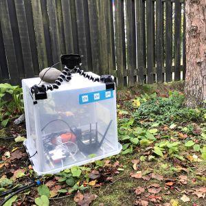 En kamera på en genomskinlig låda framför ett brunt staket.