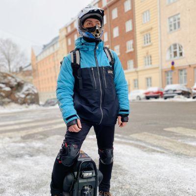 Matbudet Timur Fearless står med sin elektriska enhjuling framför gamla ståtliga hus i Främre Tölö i H:fors.