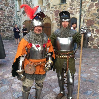 Två skådespelare står i soldatkostym från medeltiden.
