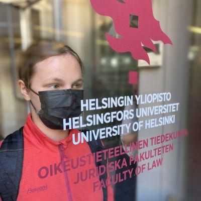 Eerika Toivola framför dörren till juridiska fakulteten.