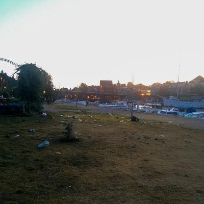 En gräsmatta fylld med skräp nere vid en hamn på natten.