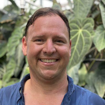 En man med kort hår tittar in i kameran och ler. Han har blå skjorta på sig, och i bakgrunden en massa tropiska växter.