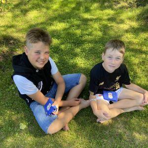 Två unga killar sitter i gräset med varsin plånbok i famnen.