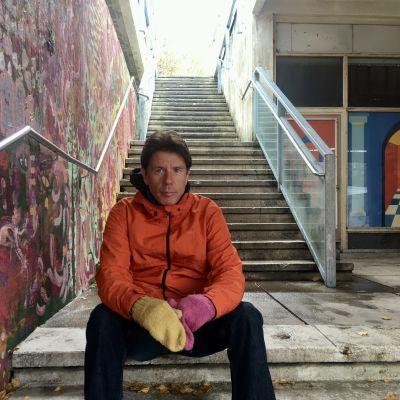 Johan Ekroth sitter i en trappa utomhus.