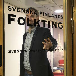 Markus Österlund öppnar glasdörr med texten Svenska Finlands Folkting.