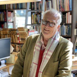 En äldre man i glasögon framför boktravar.