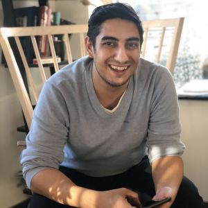 mani sitter i en gungstol framåtlutad. han bär en grå tröja och ler. i sin hand håller han sin mobil