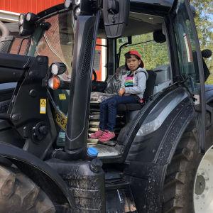 Samantha Nordmyr har fått många nya upplevelser efter att hon kom till Finland. Här provsitter hon traktorn.