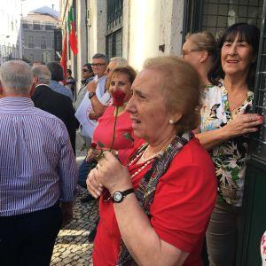 Kvinna med en röd ros i handen följer med socialisternas valtåg.