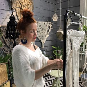 kvinna som knyter makramé