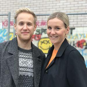 Simon Karlsson och Märta Westerlund framför graffitivägg på Yle.