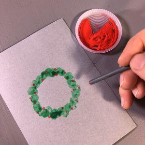 Grön krans tryckt på ett kort och nu trycks även röda bär på kransen med ändan av en pensel.