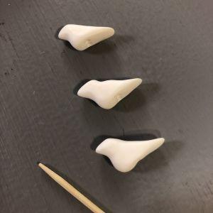 Tre fåglar formade av hobbylera, och en tandpetare ligger på ett bord
