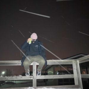 Finska snubben med skidluva sitter på staket på vintern och talar i telefon. Snö på marken.