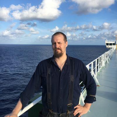 en skäggig man som står på däck på ett fartyg och i bakgrunden ser man havet.