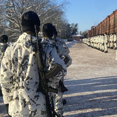 Beväringar marscherar i vinterutrustning medan andra står uppställda utanför en kasern.