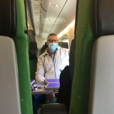 En man med kort hår, glasögon och munskydd sitter i ett tåg.