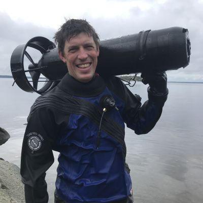 Dykaren Edd Stockdale vid en klippa. Han ler mot kameran.