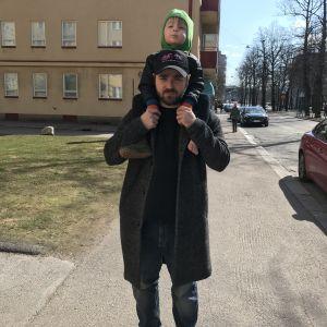 Ted står på gatan med Lo som sitter på hans axlar.
