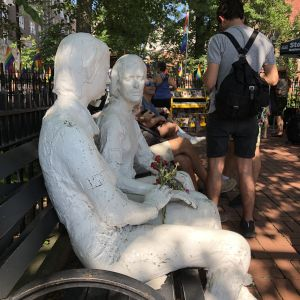 Två vita, sittande statyer i Christopher Park, med blommor i famn, personer som ledde Stonewallupproret