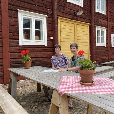 Susanne Lagus och Gunilla Sand sitter utomhus vid ett bord med papper framför sig på bordet och en röd stockvägg bakom sig.