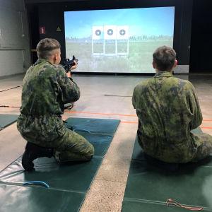 Beväringar övar att skjuta framför en stor bildskärm inne i en hall.