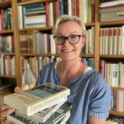 Nelly Laitinen håller i en hög med böcker framför sin bokhylla.