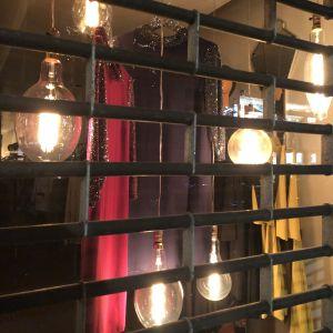 Nattstängd damklädsbutik med juldekorationer bakom gallerfönster.