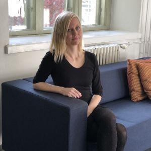Jessikka Aro i en soffa framför fönster i G-18.
