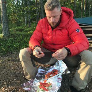 Juha Rouvinen valmistaa ruokaa metsässä.