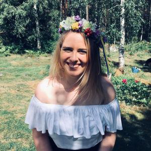 En kvinna med blont hår sitter ute i solen och skrattar. Hon har en vit blus på sig och en stor blomkrans på huvudet. Det är sommar och i bakgrunden syns björkar.