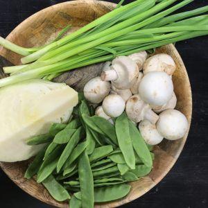 En skål med ärtor, champinjoner och andra grönsaker.