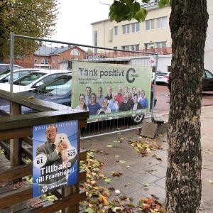 Tänk positivt, C framåt, står det på Centerns valplakat framför rivningstomt i Mariehamn