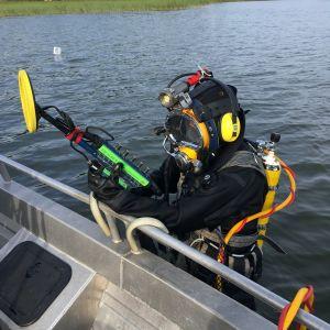 Dykare i vattnet bredvid motorbåt