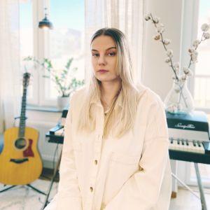 Josefin Sirén sitter ner iklädd i en vit skjorta. I bakgrunden syns en gitarr och ett piano.