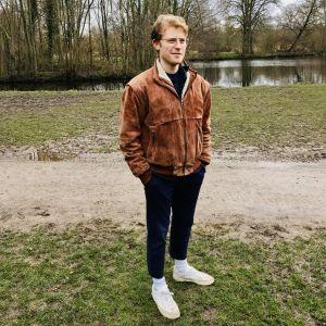23-åriga studeranden Ollie Charlton i fotograferad i en park i Amsterdam. Han är ledigt klädd. Det är fortfarande tidig vår och inga löv i träden.
