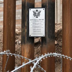 En plakett på det höga gränsstaket med  taggtråd visar att president Trump har varit här.