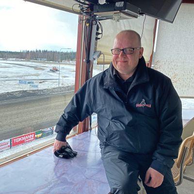Markku Sadinmaa istuu raviradan tuomaritornissa, taustalla ravihevonen