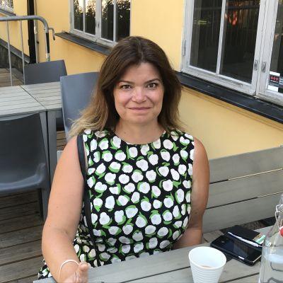 Laura Rissanen sitter vid ett bord.