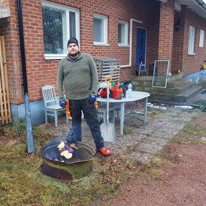 Viktor Eriksson stor framför sitt hus, bredvid en eld där han lagar mat.