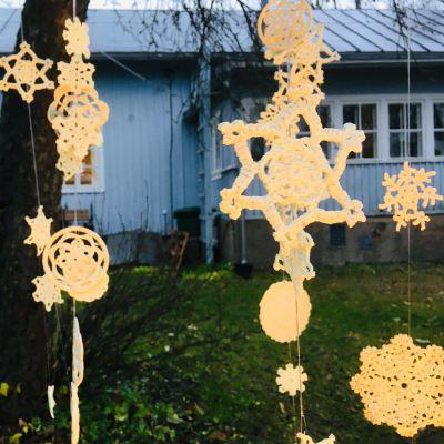 Virkade blommor och stjärnor som hänger i ett träd.