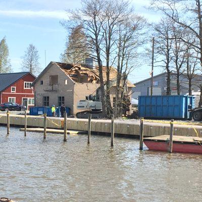 ett hus vid en å som är halvrivet. En stor del av taket är borta. Intill en hamn och en träbyggnad.