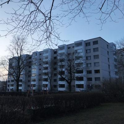 Ett vitt bostadshus med sju våningar i skymningen.