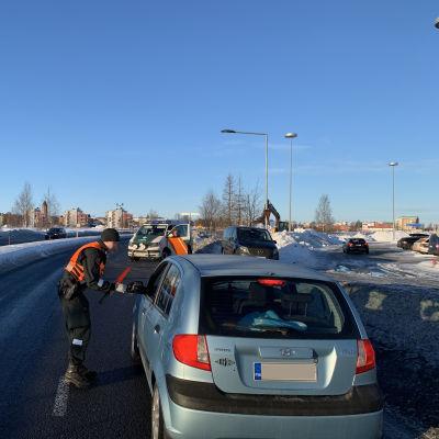 Några bilar i ett vintrigt landskap. En man i orange väst kontrollerar en ljusblå personbil som har stannat.