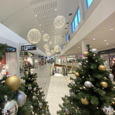 Joulukuusia ja jouluvaloja näkyy kuopiolaisen kauppakeskus Matkuksen tyhjällä käytävällä.