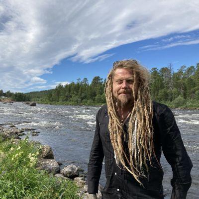Jonne Järvelä katsoo kameraan. Taustalla Juutuanjoki.