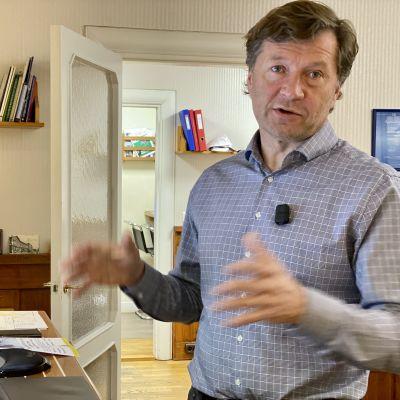 Fastighetsmäklare Risto Volanen står i sitt kontor.