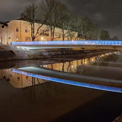 Biblioteksbron i Åbo lyser i blått och speglas i Aura å en sen natt.
